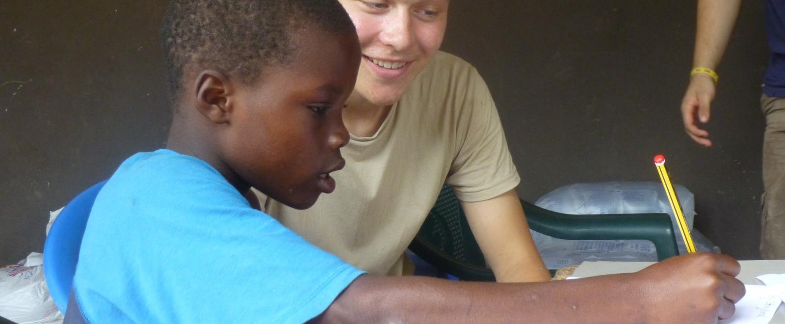 A volunteer teaching in Africa helps a child with a homework assignment at a placement in Ghana, Africa.